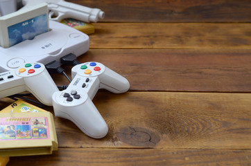 Old 8-bit video game console and many gaming accessories like a joysticks and cartridges