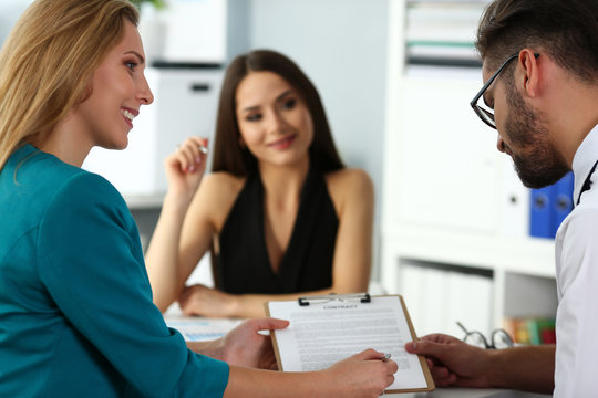 Beautiful brunette clerk discuss financial paper issues with family couple visitors portrait. Loan fraud credit mortgage bank agent strike bargain job offer hire real estate legal agency notary sale