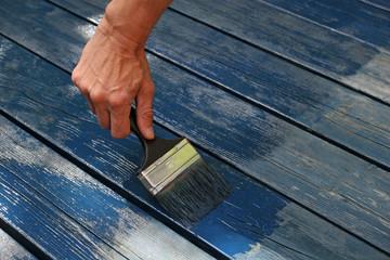 Anstrich einer Holzterrasse mit blauer Farbe