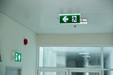 Sign : Emergency exit sign at path way indoor building public facility that emergency escape route is left. (fire, building, health or safety) require exit signs to be permanently lit Wall mural