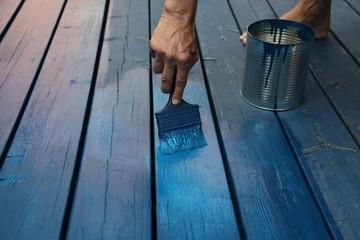 Anstreichen einer Holzterrasse mit blauer Farbe