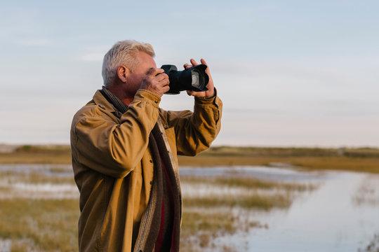 Senior Man Focusing his Camera