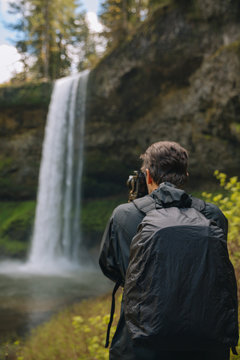 Photographer shooting images of a waterfall in the Pacific Northwest.