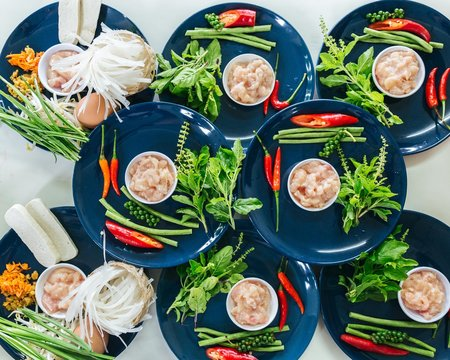Raw ingredients for Thai food cooking class organized on blue plates