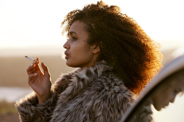 young woman in furry coat smoking cigarette