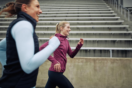 Smiling women running together on a track outdoors