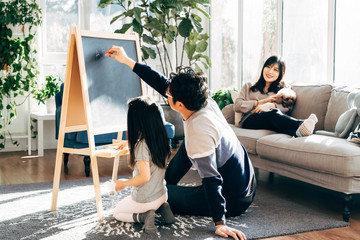 Young father and daughter painting at home, while mother is sitting on sofa with dog