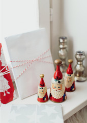 Christmas decoration in the shape of Santa Claus and some wrapped gift by the window