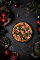 Tasty pomegranates and kale vegan pizza on a dark table