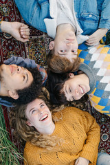 Laughing friends lying on carpet in nature
