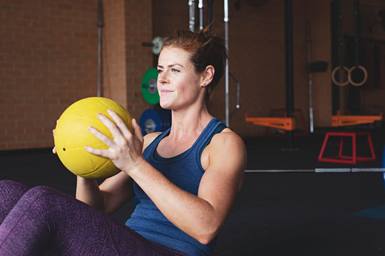 Healthy and fit, authentic woman exercising with a weighted ball in an indoor gym