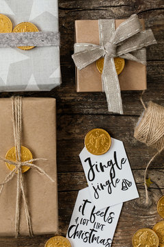 Diy christmas gifts wrapped with starry and kraft paper with hand written cards and golden chocolate coins