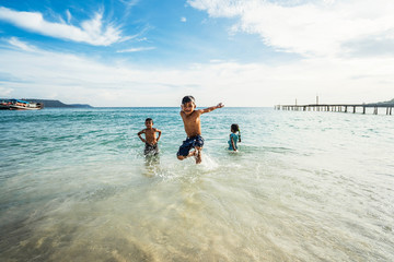 Group of cute Asian kids having fun in the beach