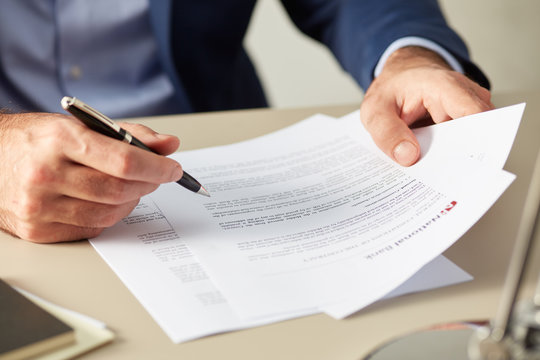 Manager in suit reading paper document