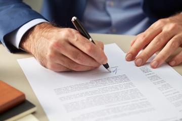 Faceless man signing paper