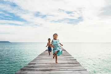 Asian kids running on pier of beach
