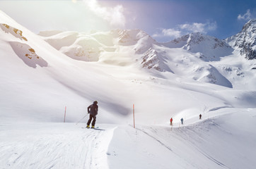 Several skiers skiing down the slope in beautiful snowy mountain landscape