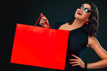 Black Friday sale concept for shop. Happy smiling woman in sunglasses holding big red bag isolated on dark background at shopping. Copy space for text.