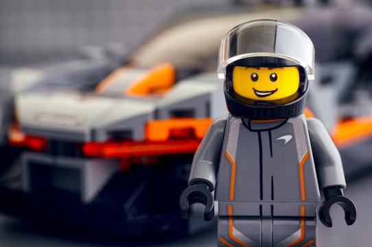 Tambov, Russian Federation - April 21, 2019 Lego McLaren Senna driver minifigure by LEGO Speed Champions against his car. Studio shot.