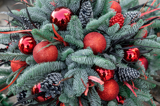 Winter decor. Beautiful arrangement of christmas tree red balls, cones, natural spruce branches for indoor outdoor festive decorating the house for the Christmas New Year holidays.