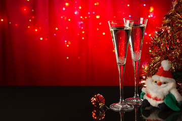 Two champagne glasses, Santa Claus and red Christmas ball on a reflective surface on a red background. Christmas bright background. The form is ready to add text or a picture.