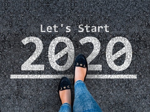 happy new year 2020. lets start 2020. woman legs in shoeas  walks on asphalt road next to number 2020