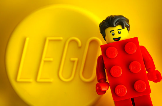 Tambov, Russian Federation - May 20, 2018 Lego Red Suit Brick Guy minifigure against yellow background with word LEGO. Studio shot.