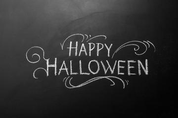 Chalk inscription happy Halloween on blackboard