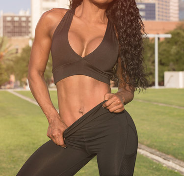 Closeup Outdoor Front Portrait of a African American Fitness Model in Black Sportswear Showing Her Abs