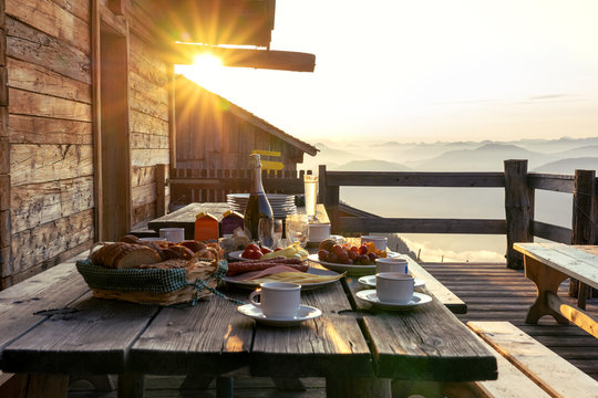Breakfast table in rustic wooden terace patio of a hut hutte in Tirol alm at sunrise