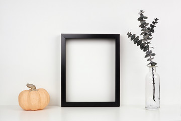 Mock up black frame with pumpkin decor and eucalyptus branch on a shelf or desk. Autumn concept. Portrait frame against a white wall.