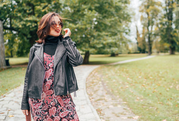 Wall Mural - Smiling female dressed boho fashion style colorful long dress with black leather biker jacket with brown leather flap bag having a autumn park walking.