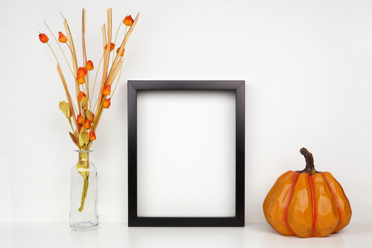 Mock up black frame with fall branches and pumpkin decor on a shelf or desk. Autumn concept. Portrait frame against a white wall.