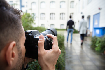 Man Taking Photograph Of Couple Walking Together At Outdoors