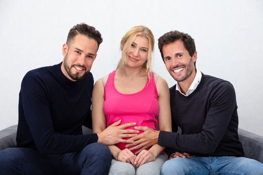Smiling Men Touching The Belly Of Pregnant Surrogate Woman