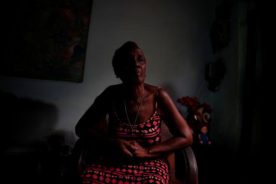 Marta Insua, who says she decided to avoid turning on lights to save energy, rests on a chair at her home in Havana