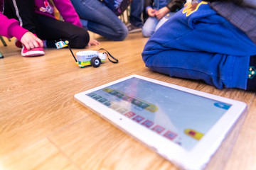 Valencia, Spain - April 13, 2019: Children using a robot motorized, reconfigurable education toy, created with Lego WeDo blocks programmable through a tablet or mobile.