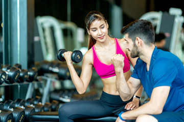 Trainer or instructor man is teaching asian spoty woman lifting a dumbbell and exercise in the gym. Smiling Woman Using Hand Weights While Personal Trainer Supervises Her Progress