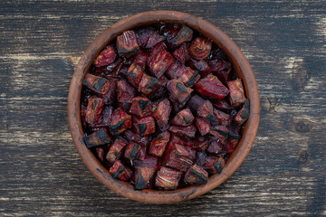 Baked red beetroot with honey on the wooden table, closeup. Ceramic bowl with purple beet slices background, top view