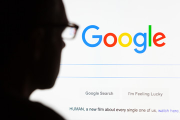 BATH, UK - SEPTEMBER 12, 2015: Close-up of the Google.com search homepage displayed on a LCD computer screen with the silhouette of a man's head out of focus in the foreground.