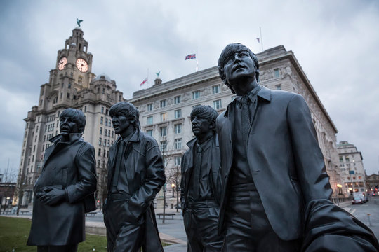 LIVERPOOL, UK - March 18, 2018 : Close up of the Beatles statues at the pier head in Liverpool with the Royal Liver Building in the background.