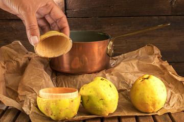 Imagination d'un fruit prêt à l'emploi - Coing ouvert en 2 comme une poupée russe avec 2 autres coings et une casserole en cuivre pour préparation de confiture - image nature morte rustique et vintage
