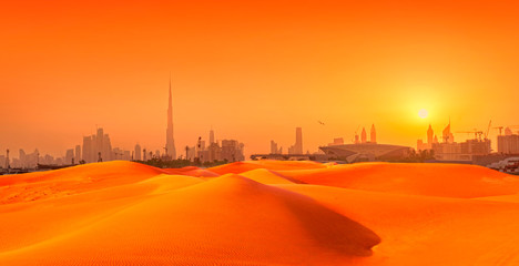 Dubai cityscape panorama with sand dunes at sunset. composite image of city and sand