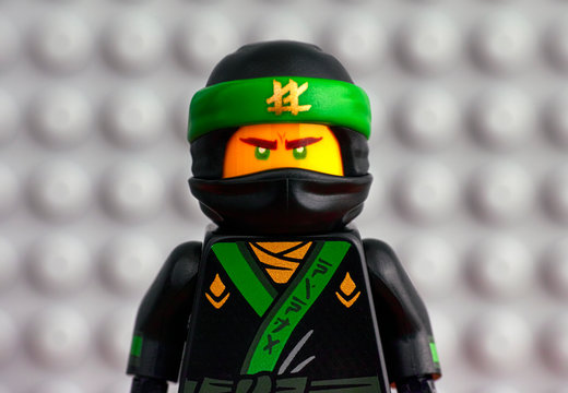 Tambov, Russian Federation - July 29, 2018 Portrait of Lego The Green Ninja against gray baseplate background.
