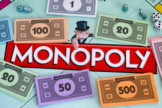 Tambov, Russian Federation - January 26, 2018 Center of Monopoly gameboard with money packs tokens and dice.