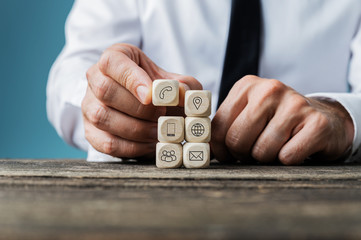 Stacking wooden dices with contact and information icons on them