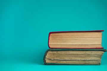 Beautiful old books on a table aquamarine background.