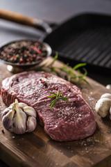 Rib Eye steak salt pepper spices garlic and mushroom. Raw beef meat on butcher board