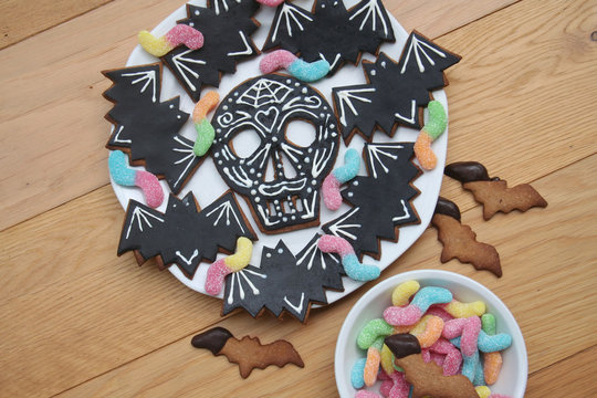 Halloween cookies in shape of skull and bat with colorful worm candies on a plate on wooden background. Halloween sweet food