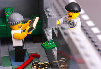 Tambov, Russian Federation - January 08, 2017 Lego bank burglary. Two robbers broke bank wall and take out money and gold. Studio shot.
